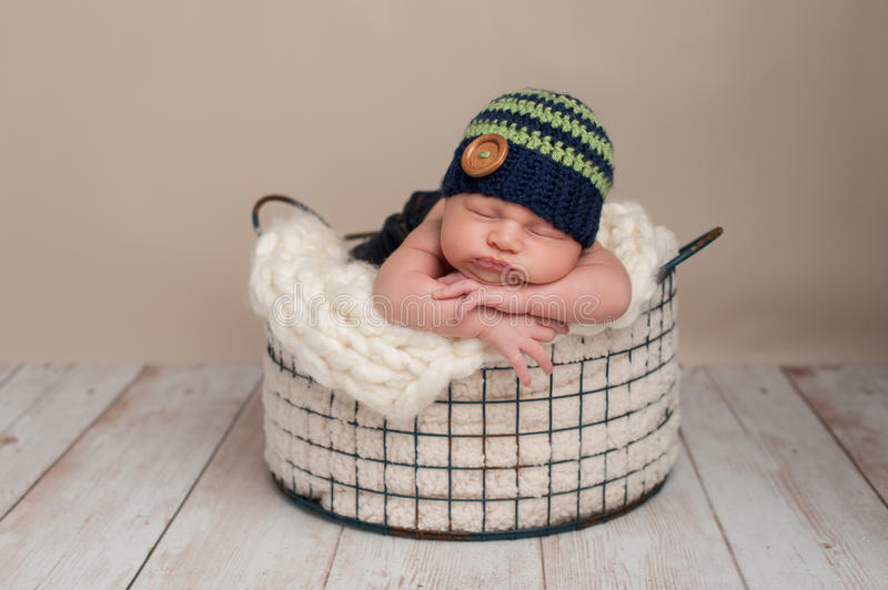 Newborn Baby Boy Wearing a Beanie Cap. Three week old newborn baby boy wearing jeans and a crocheted blue and green beanie hat. He is sleeping on his stomach in stock photo