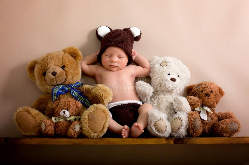 Newborn baby boy wearing a brown knitted bear hat and pants, sleeping on a shelf stock images