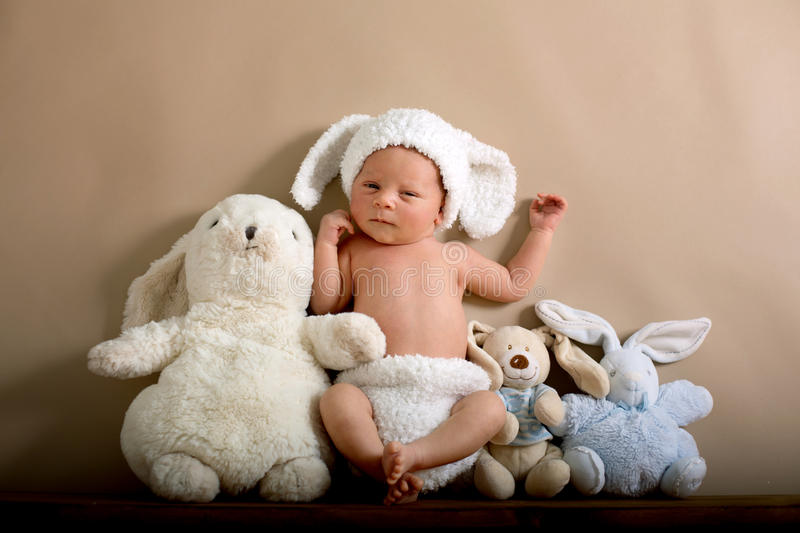 Newborn baby boy wearing a brown knitted rabbit hat and pants, s. Leeping on a shelf next to little fluffy rabbits. Shot in the studio on a creamy background stock images