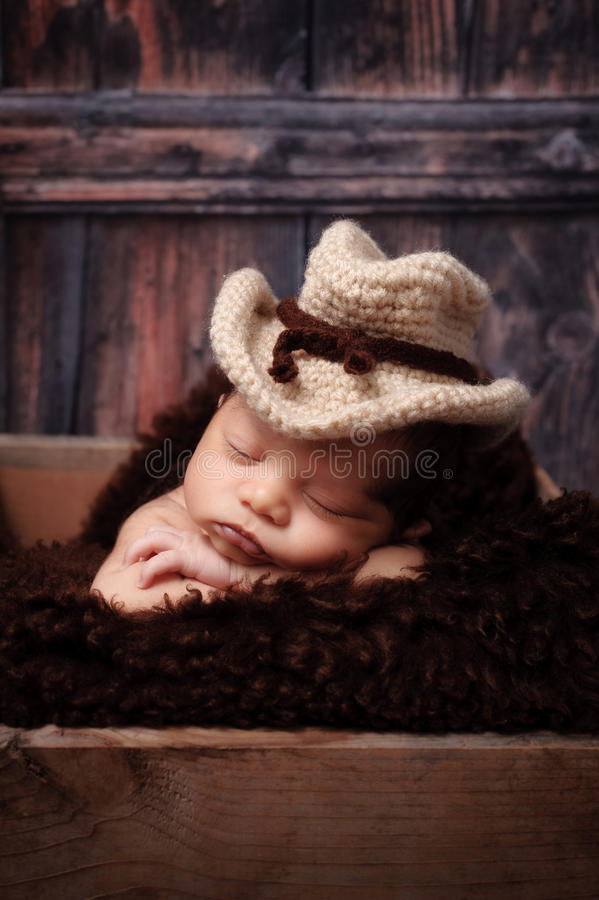 Newborn Baby Boy Wearing a Cowboy Hat. 9 day old newborn baby boy wearing a crocheted cowbow hat and sleeping on his stomach in a wooden crate. Shot in the stock photos