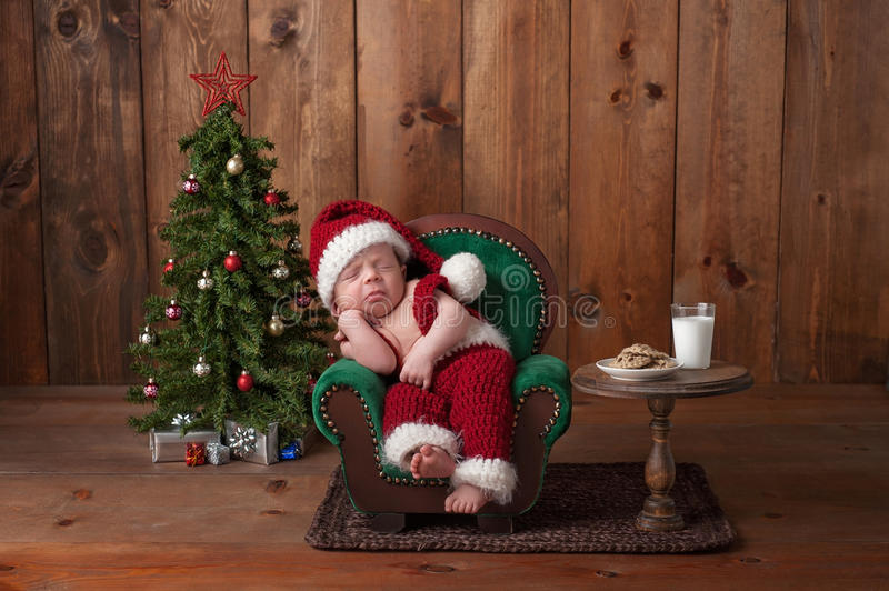Newborn Baby Boy Wearing a Santa Suit. Two week old, newborn, baby boy wearing a crocheted Santa suit. He is sleeping on a tiny armchair. Shot in the studio with stock photo