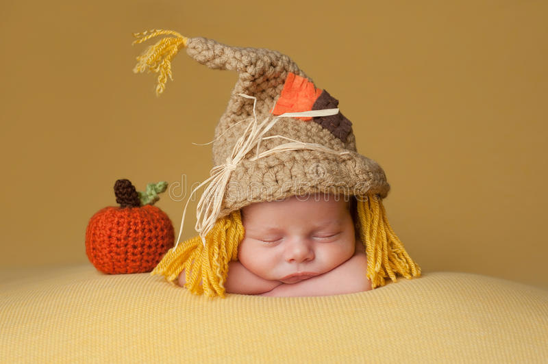 Newborn Baby Boy Wearing a Scarecrow Hat. Four week old newborn baby boy wearing a crocheted scarecrow hat. He is sleeping on a gold blanket next to a crocheted stock photography