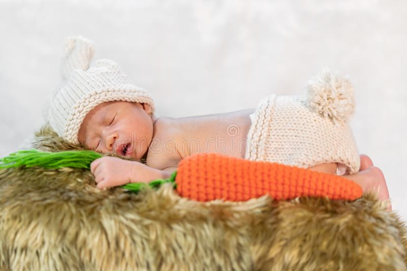 Newborn baby in bunny costume sleeping on fur bed. Newborn baby in bunny costume sleeping on a fur bed stock images