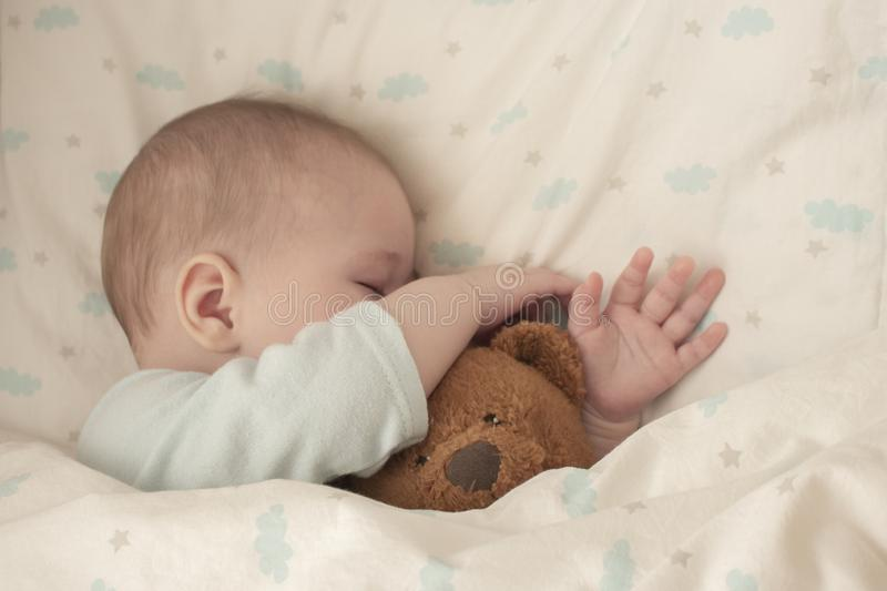 Newborn baby child asleep hugging a bear. Sleeping baby girl boy hid his nose in a teddy bear. Close-up soft focus stock photography