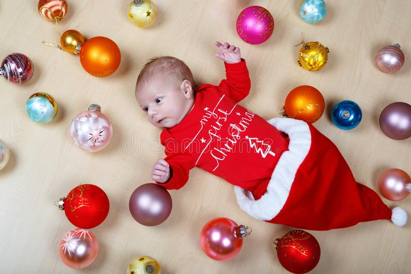 Newborn baby with Christmas tree decoarations and colorful toys and balls royalty free stock images