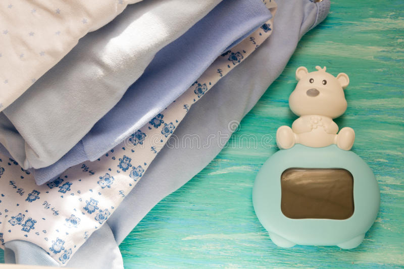 Newborn baby clothes and blue on wooden background children's room, the pile accessories. On table Mother care stock images