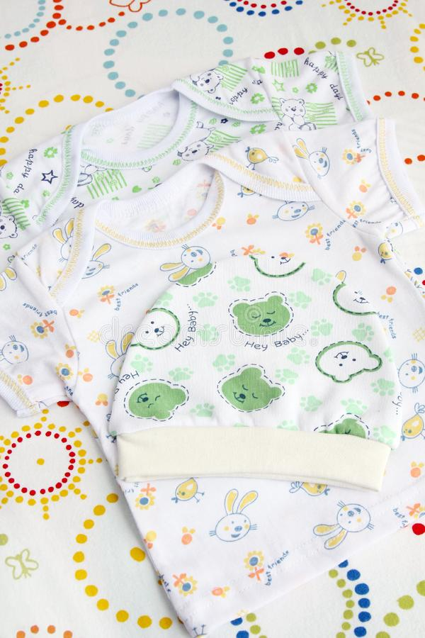 Newborn baby clothes set: two t-shirts and knitwear toddler hat stock photo