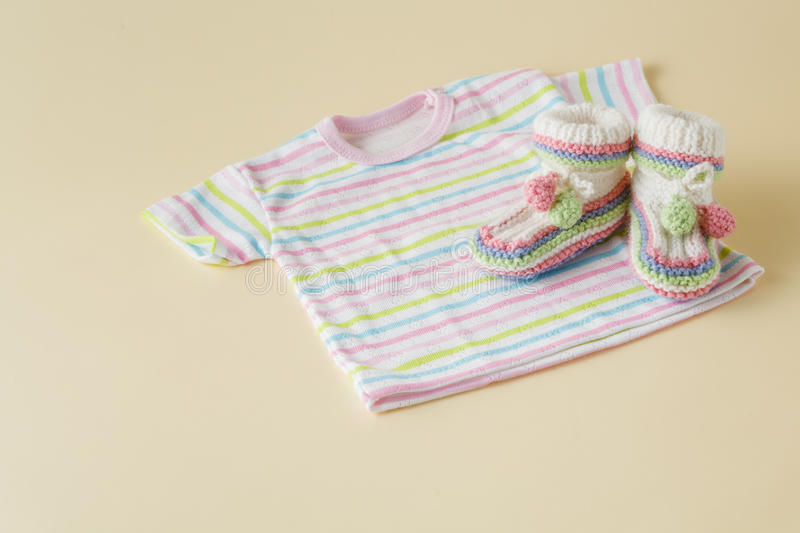 Newborn baby clothes and shoes on beige background stock images