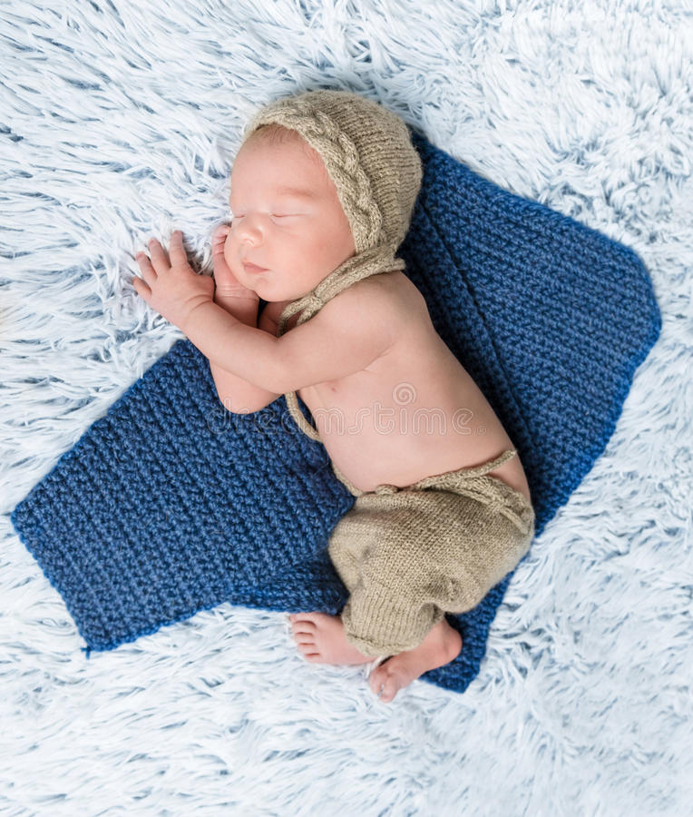 Newborn baby in costume lying on blue blanket royalty free stock photos