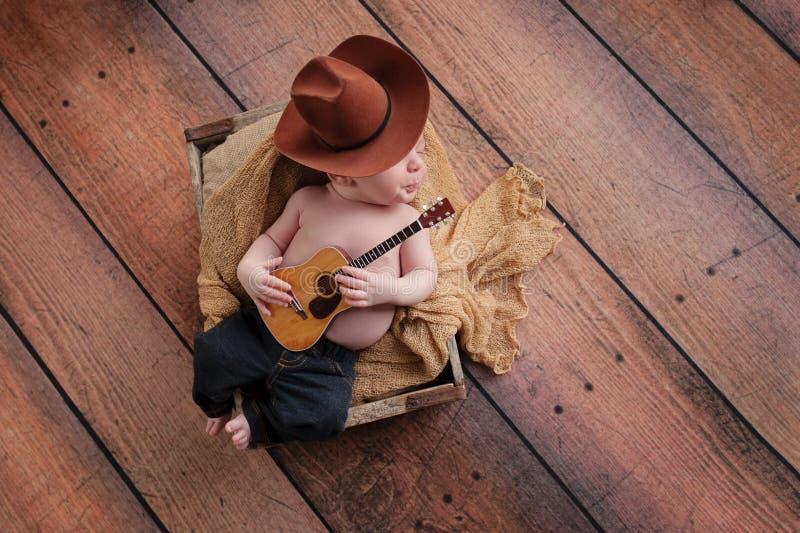 Newborn Baby Cowboy Playing a Tiny Guitar stock photo