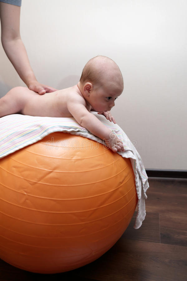 Newborn baby exercising on a gymnastic ball. At home stock photography