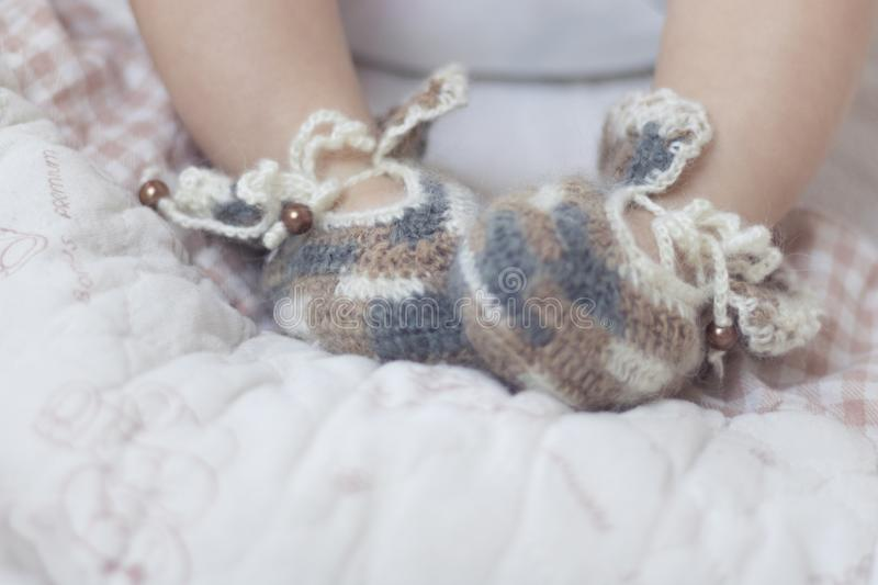 Newborn baby feet close up in brown knitted socks booties on a white blanket. The baby is in the crib stock image