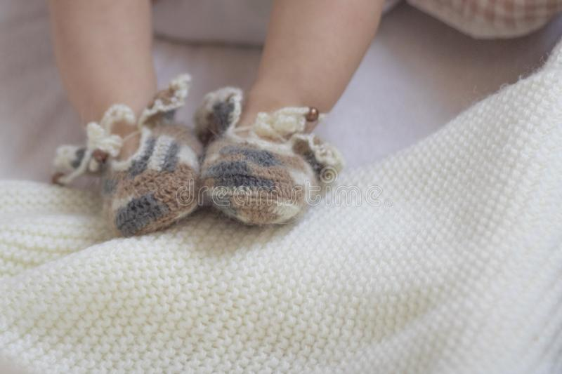 Newborn baby feet close up in wool brown knitted socks booties on a white blanket. The baby is in the crib. copyspace. Newborn baby feet close up in wool socks stock image