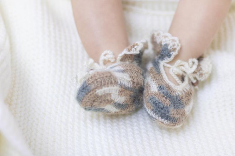 Newborn baby feet close up in wool brown knitted socks booties on a white blanket. The baby is in the crib stock photo