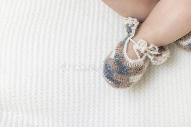 Newborn baby feet close up in wool brown knitted socks booties on a white blanket. The baby is in the crib. In the right corner. royalty free stock photography