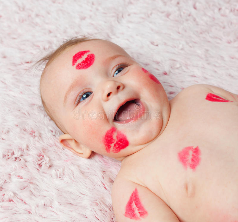 Newborn baby gir filled kisses. Newborn baby girl on the soft blanket filled kisses made with the lipstick stock photo
