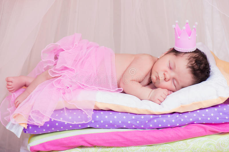 Newborn baby girl in a crown sleeping on the bed of mattresses. Fairy Princess and the Pea.  royalty free stock photography