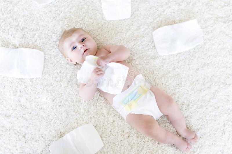 Newborn baby girl with diapers. Dry skin and nursery. Cute adorable newborn baby of 3 moths with diapers. Hapy tiny little girl or boy looking at the camera. Dry royalty free stock photography