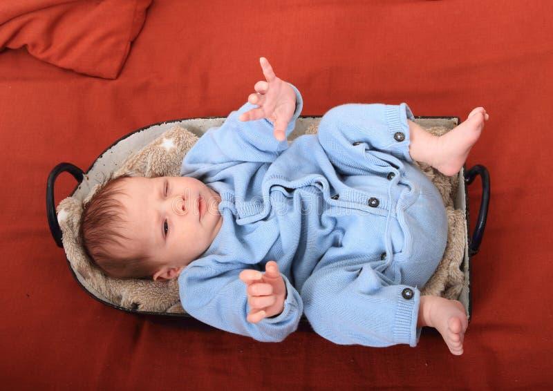 Newborn baby girl in baking pan. Newborn baby girl dressed in blue baby jumpsuit lying in baking pan royalty free stock images