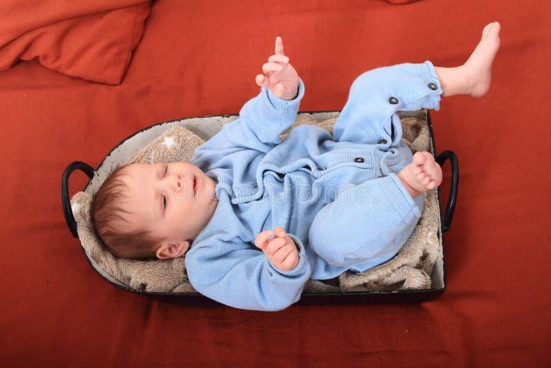 Newborn baby girl in baking pan. Newborn baby girl dressed in blue baby jumpsuit lying in baking pan royalty free stock photo