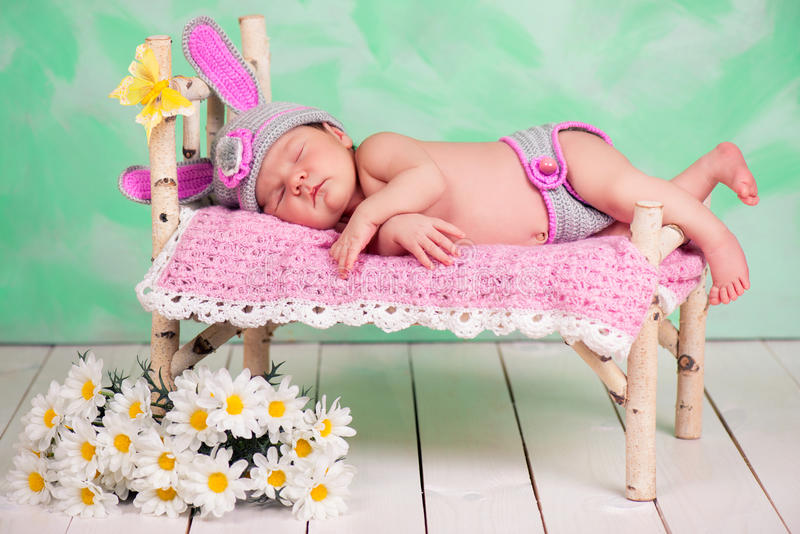 Newborn baby girl in a knitted hare costume sleeping on a wooden crib birch.  stock photo