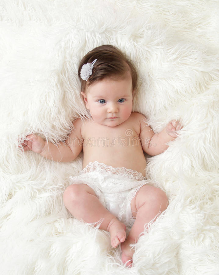 Newborn Baby. Girl posed in a bowl on her back, on blanket of fur, smiling looking at camera stock images