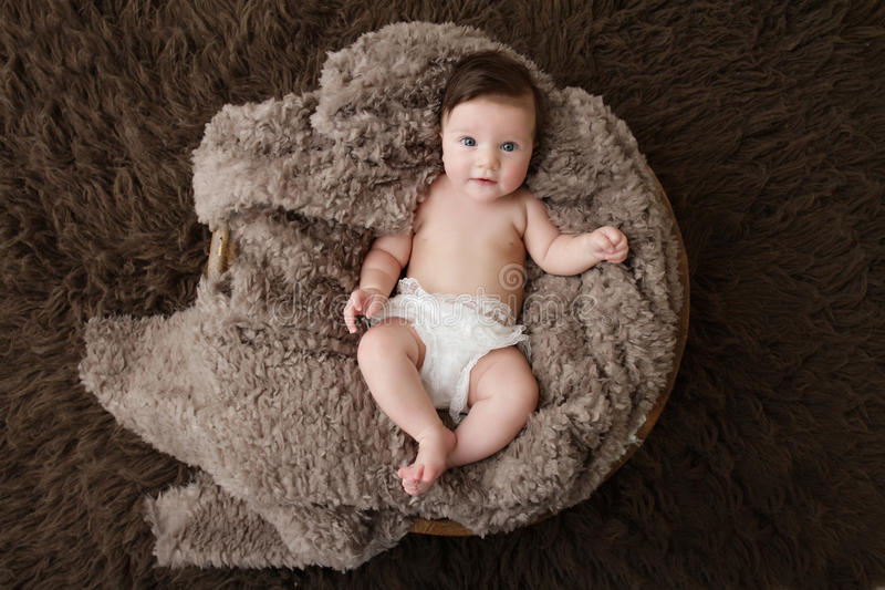 Newborn Baby. Girl posed in a bowl on her back, on blanket of fur, smiling looking at camera royalty free stock image