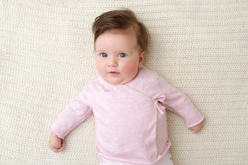 Newborn Baby. Girl posed in a bowl on her back, on knit blanket, smiling looking at camera stock photos