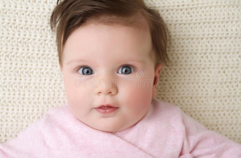 Newborn Baby. Girl posed in a bowl on her back, on knit blanket, smiling looking at camera royalty free stock photo