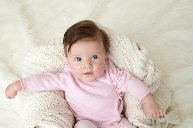 Newborn Baby. Girl posed in a bowl on her back, on knit blanket, smiling looking at camera stock photography