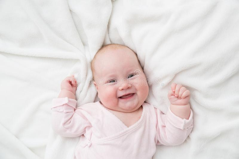 Newborn baby girl posed on her back, on blanket of fur, smiling looking at camera.  stock photos