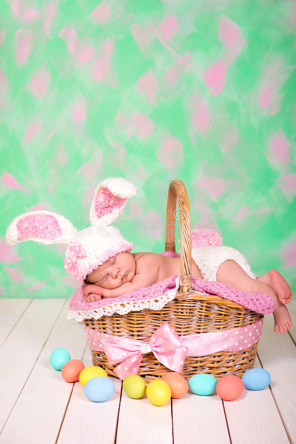 Newborn baby girl in a rabbit costume has sweet dreams on the wicker basket. Easter Holiday.  royalty free stock images