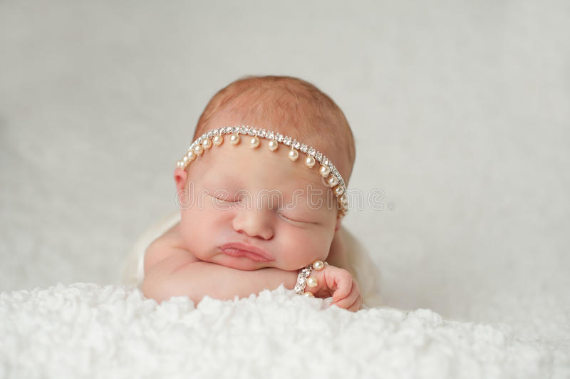 Newborn Baby Girl with Rhinestone and Pearl Headband. Portrait of a red headed, 2 week old, newborn baby girl. She is wearing a rhinestone and pearl headband and stock image