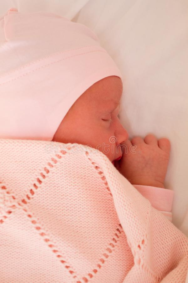 Newborn baby girl sleeping in a cradle stock photography
