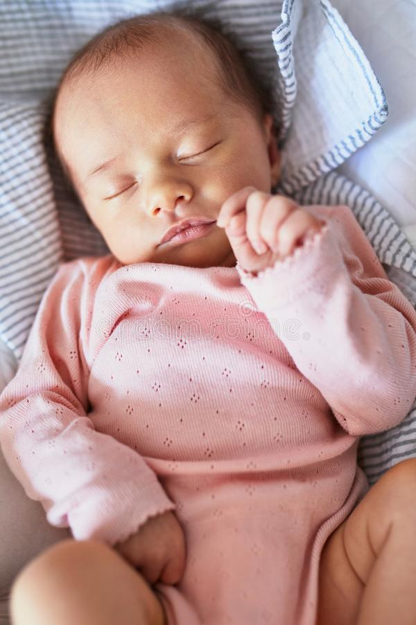 Newborn baby sleeping. Newborn baby girl sleeping peacefully in the crib royalty free stock images