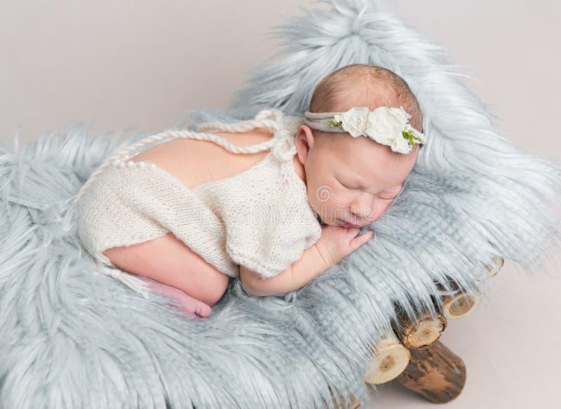 Newborn baby girl sleeps on small wooden crib. Sweet newborn baby girl with headband sleeps on small wooden crib royalty free stock photos