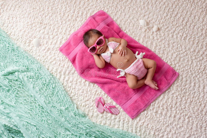 Newborn Baby Girl Wearing a Bikini and Sunglasses. Four week old newborn baby girl sleeping on a pink towel. She is wearing a crocheted pink and white bikini and royalty free stock photography