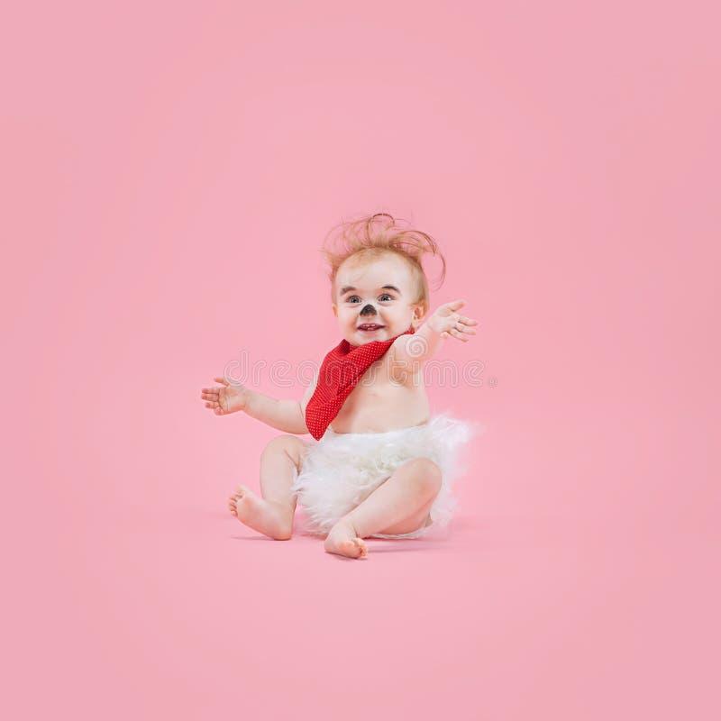 Newborn baby girl wearing a Halloween costume. On pink studio background royalty free stock photo