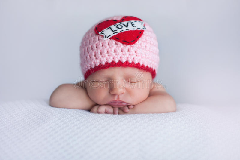 Newborn Baby Girl Wearing a. Portrait of a seven day old sleeping baby girl wearing a crocheted Love beanie. Cute shot to use for Valentine's Day royalty free stock photos