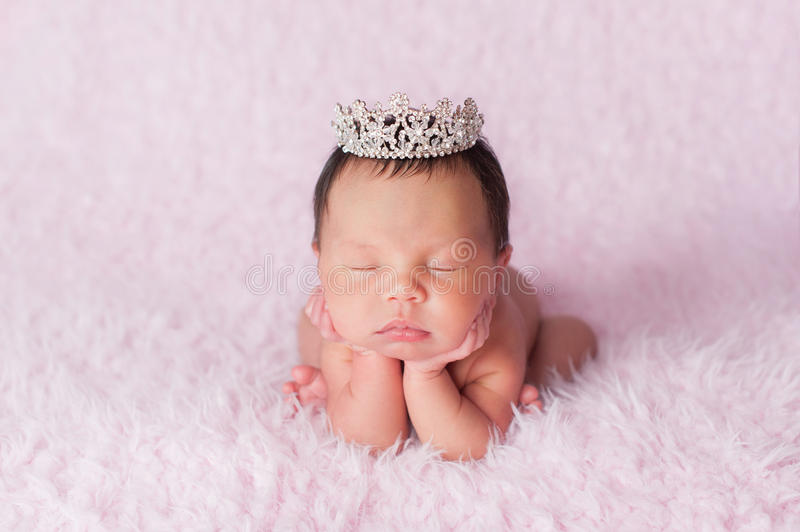 Newborn Baby Girl Wearing a Rhinestone Princess Crown. Portrait of nine day old sleeping newborn baby girl. She is wearing a rhinestone crown and is posed with royalty free stock photo