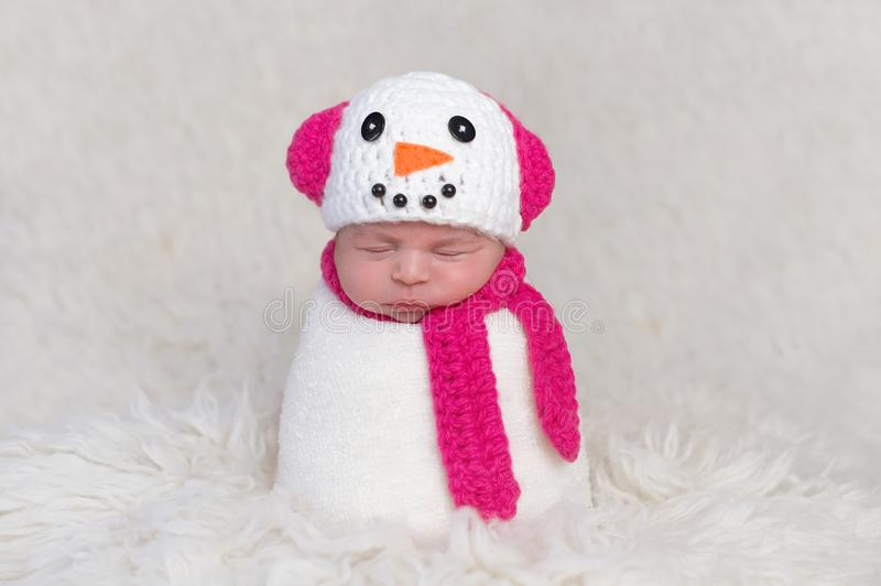 Newborn Baby Girl Wearing a Snowgirl Costume. A newborn baby girl wearing a crocheted, bright pink and white snowgirl cap with matching neck scarf. Photographed stock image