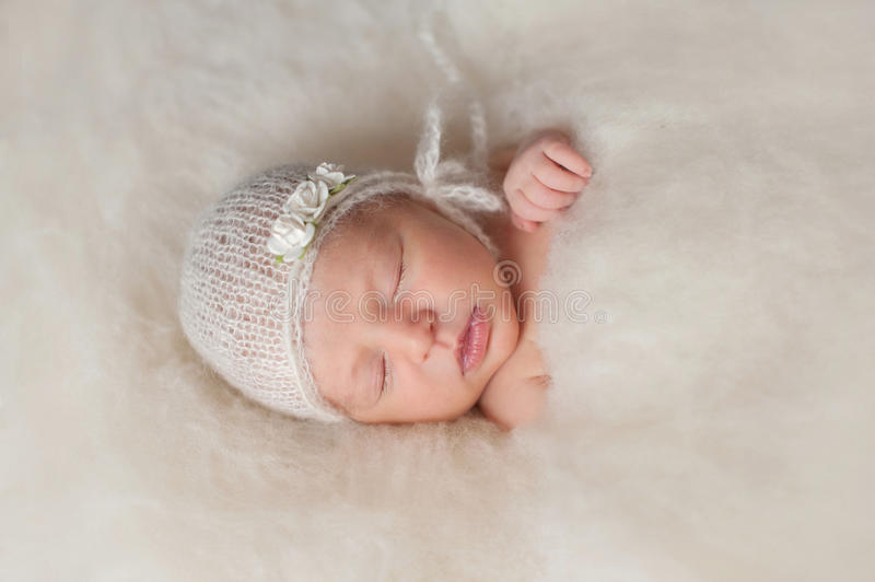 Newborn Baby Girl Wearing a White Knitted Bonnet. A portrait of a beautiful seven day old newborn baby girl wearing a white, knitted, mohair bonnet and rose stock images