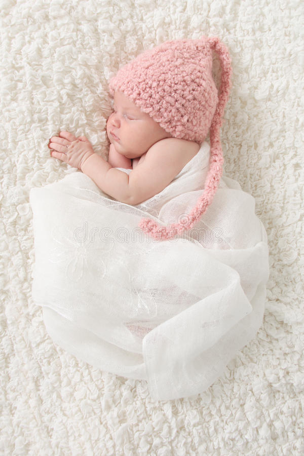 Newborn baby girl. Wrapped in vintage lace, wearing a pink knitted hat stock photos