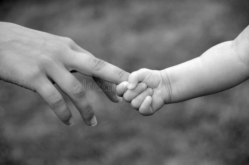 Newborn baby grasp. Newborn grasping parent's finger stock image