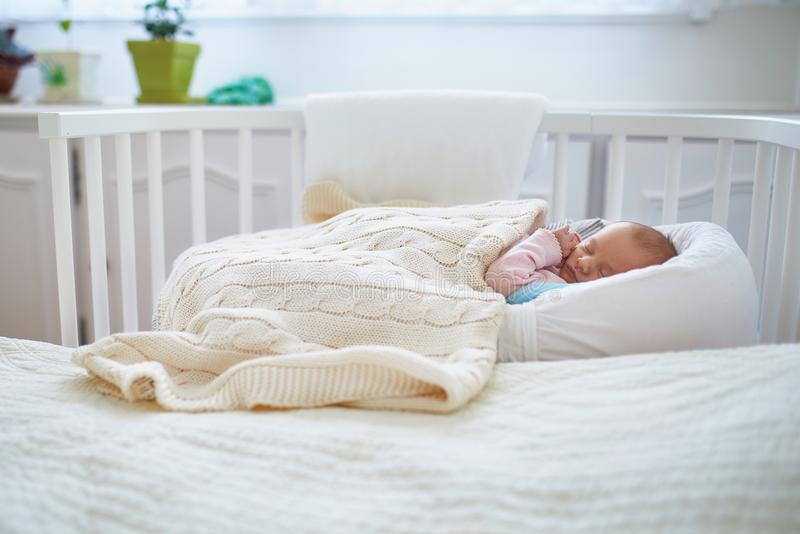 Newborn baby having a nap in co-sleeper crib attached to parents` bed royalty free stock photo