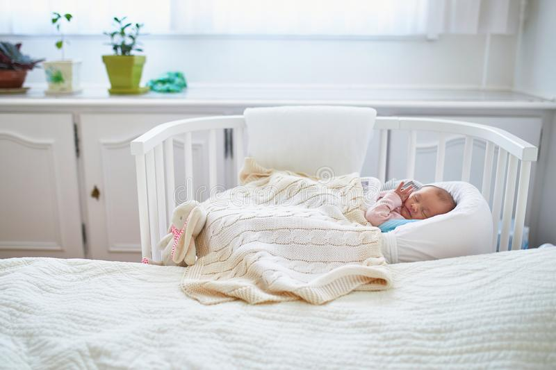 Newborn baby having a nap in co-sleeper crib attached to parents` bed. Newborn baby girl having a nap in co-sleeper crib attached to parents` bed royalty free stock image