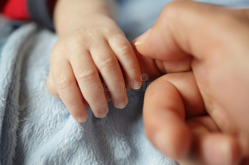 Newborn baby holding hands with dad royalty free stock image