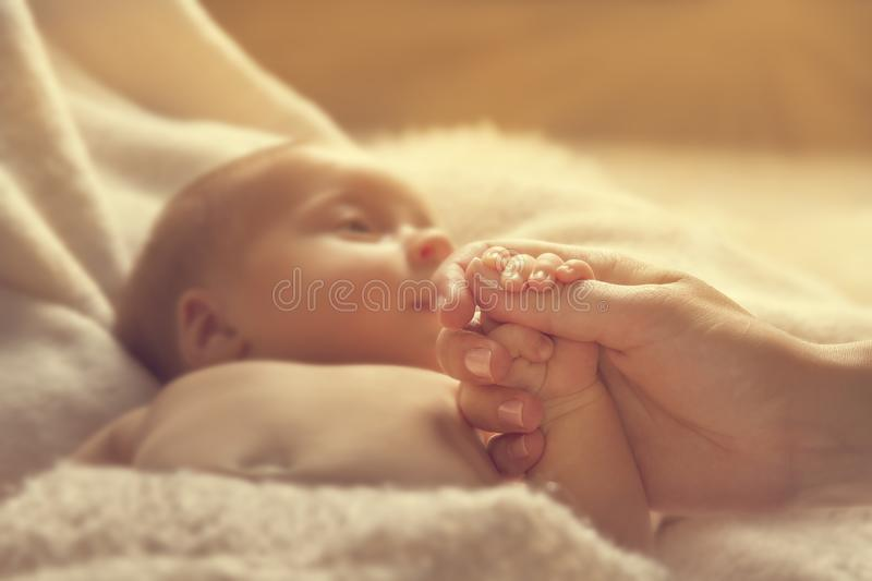 Newborn Baby Holding Mother Hand, New Born Child and Parent. Selective Focus on Family Hands, Kid and Woman stock photography