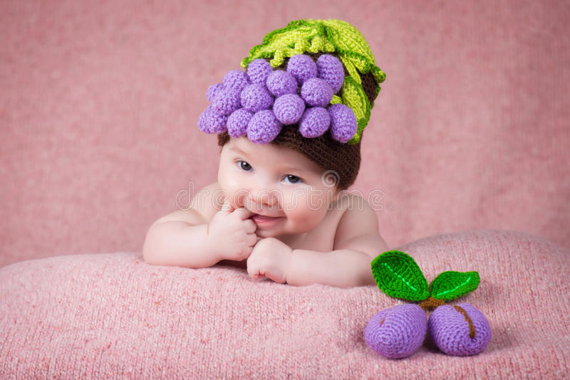 Newborn baby a knitted cap in the form of grapes. royalty free stock photo