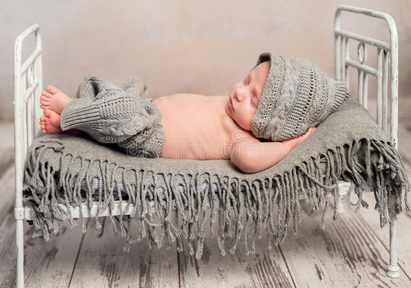 Newborn baby in knitted hat and pants sleeping on old cot. Funny newborn baby in knitted hat and pants sleeping on old retro cot with plaid with hands behind stock photography